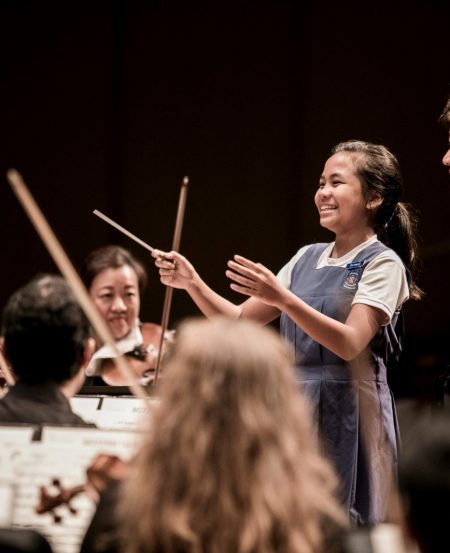 "A young audience member tries her hand at conducting at the ""SSO in Your Community"" concert, Agape Auditorium, Paya Lebar Methodist Girls' School. (Photo Credit: Chrisppics+)"