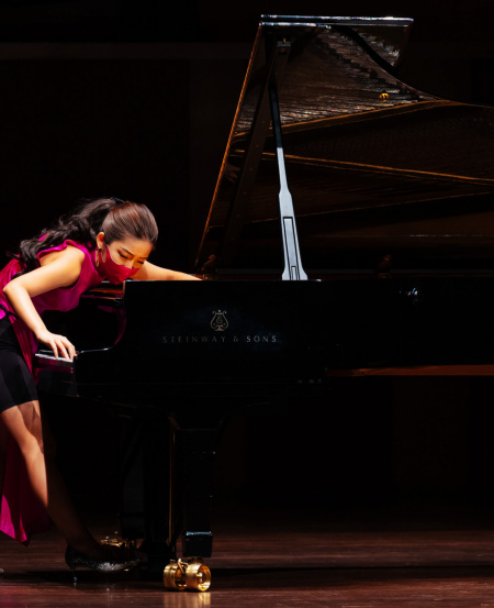 """In Churen Li's recital of Crumb's """"Five Pieces for Piano"""", her technique involved plucking and strumming the piano strings with her fingers, and placing a metal paperclip on the vibrating strings to produce a metallic sound.  [Photo credit: Nathaniel Lim]"""
