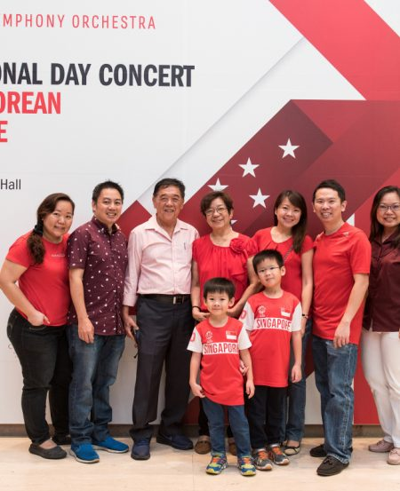 Concertgoers gear up in red in front of our photowall